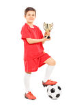 Full length portrait of junior football player holding a trophy royalty free stock photography