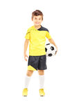 Full length portrait of a kid in sportswear holding a soccer ball. Isolated on white background stock images