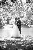 Full length portrait of kissing bride and groom at park near the Stock Photography