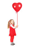 Full length portrait of a little girl holding a red heart shaped. Balloon  on white background Royalty Free Stock Image