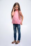 Full length portrait of a little girl talking on the phone Stock Photography