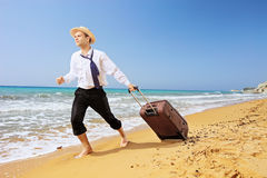 Full length portrait of a lost businessman carrying a suitcase a. T sandy beach Royalty Free Stock Photography