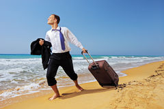 Full length portrait of lost man carrying a bag. Full length portrait of a lost businessman carrying a suitcase at the beach Royalty Free Stock Image