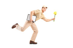 Full length portrait of a mailman delivering flowers Stock Photos