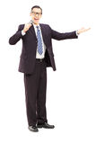 Full length portrait of a male announcer holding microphone Royalty Free Stock Image
