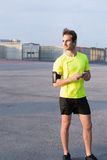 Full length portrait male athlete standing in the road while takes a break after an intense fitness training outdoors. Young male runner completes training while Stock Photography
