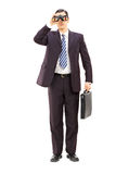 Full length portrait of male businessman watching through binocu Stock Photo