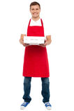 Full length portrait of male chef holding pie box Royalty Free Stock Images
