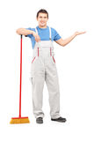 Full length portrait of a male cleaner with a broom gesturing Royalty Free Stock Image