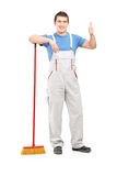 Full length portrait of a male cleaner with a broom giving thumb Stock Images