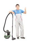 Full length portrait of a male cleaner with a vacuum cleaner giv Stock Photography