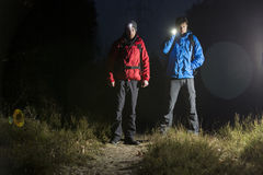 Full length portrait of male hikers with flashlights in field at night stock image