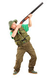 Full length portrait of a male hunter shooting with a shotgun. On white background Stock Photo