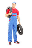 Full length portrait of a male mechanic holding a vehicle tires Royalty Free Stock Photography