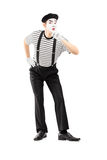 Full length portrait of a male mime artist gesturing silence. With a finger on his mouth, isolated on white background Stock Photo