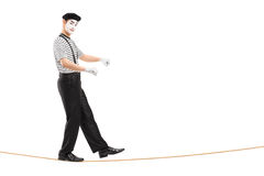 Full length portrait of a male mime artist walking on a rope Stock Photo