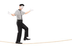 Full length portrait of a male mime artist walking on a rope Royalty Free Stock Image