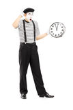 Full length portrait of a male mime holding a clock and gesturin Stock Image