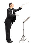 Full length portrait of a male orchestra conductor directing wit. H stick isolated against white background Stock Photos