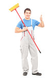 Full length portrait of a male painter holding a roller and givi Stock Photography