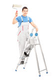 Full length portrait of a male painter holding a roller and stan. Ding on a ladder isolated on white background stock image