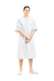 Full length portrait of a male patient in a hospital gown. Isolated on white background stock photography