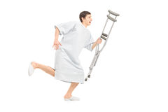 Full length portrait of a male patient running and holding a cru. Tch, isolated on white background Stock Images