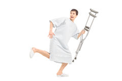 Full length portrait of a male scared patient running and holdin Royalty Free Stock Photo