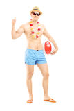 Full length portrait of a male in shorts, holding a ball. Full length portrait of a male in swimming shorts, holding a beach ball and giving thumb up, isolated Stock Images