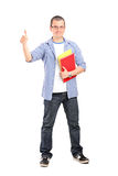 Full length portrait of male student with books giving thumb up. Isolated on white background Royalty Free Stock Image