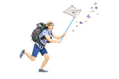 Full length portrait of a male tourist catching butterflies with Royalty Free Stock Image