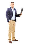 Full length portrait of a man holding a laptop. Isolated on white background royalty free stock photo