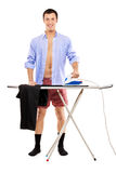 Full length portrait of a man ironing. A full length portrait of a man ironing on a ironing board his pants isolated on white background stock image
