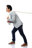Full length portrait of a man pulling rope. Over white background Stock Photo