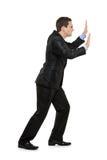 Full length portrait of a man pushing something Stock Photography