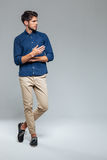 Full length portrait of a man standing with legs crossed Stock Image