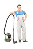 Full length portrait of a man in uniform posing with a vacuum cl Stock Photo