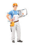 Full length portrait of a manual worker with a helmet carrying a Royalty Free Stock Photography