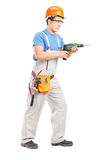 Full length portrait of a manual worker with helmet using a dril Royalty Free Stock Photos