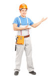 Full length portrait of a manual worker with tool belt and helme. T gesturing on white background stock photo