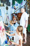 Senior Art Teacher Working with Kids. Full length portrait of mature art teacher watching group of children painting in art class stock images