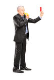 Full length portrait of a mature businessman blowing a whistle  Royalty Free Stock Images