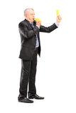 Full length portrait of a mature businessman blowing a whistle a Stock Image