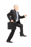 Full length portrait of a mature businessman doing a huge step Royalty Free Stock Photography