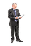Full length portrait of a mature businessman looking at document Stock Photo