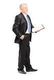 Full length portrait of a mature businessman posing with clipboa Royalty Free Stock Photos