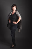 Full Length Portrait Mature Dark-Haired Woman with a Serious Expression. On Dark Background royalty free stock image