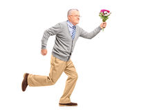 Full length portrait of a mature gentleman running with flowers royalty free stock photo