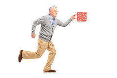 Full length portrait of a mature gentleman running with a gift b Royalty Free Stock Photography