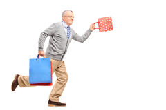 Full length portrait of a mature gentleman running with shopping Royalty Free Stock Photo